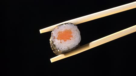 kaviár : Sushi in chopsticks on black background Stock mozgókép