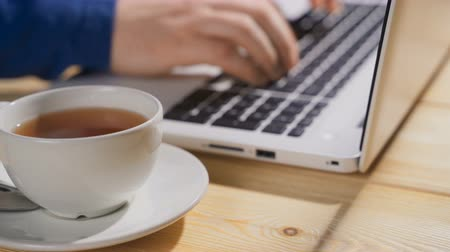 anônimo : Close up on hands of anonymous man working on laptop with cup of hot tea, focus on the cup of hot tea
