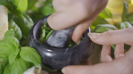 condimento : A vintage pestle while a woman is working to prepare italian pesto