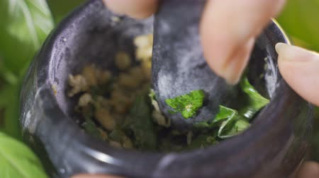 orzechy włoskie : A vintage pestle while a woman is working to prepare italian pesto