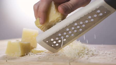 strouhaný : Woman rubs hard grated cheese. Hands and grater close-up Dostupné videozáznamy