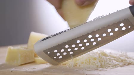négyszögletes : Chef grating Italian parmesan cheese with metal grater in the kitchen