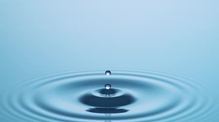Splashing Drop Of Water In Slow Motion - Water Drop in Slow Motion hits Calm Water Surface at 1000fps. Stock Footage