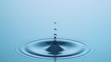 Splashing Drop Of Water In Slow Motion - Water Drop in Slow Motion hits Calm Water Surface at 1000fps. Stock mozgókép