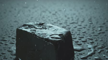 Raindrops falling on a black stone in slow motion