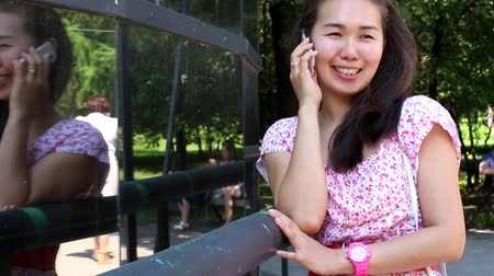 telefon : beautiful Asian girl speaks by phone Stock mozgókép