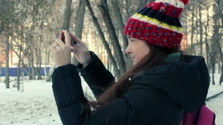 memórias : young woman takes video on your smartphone in the winter park