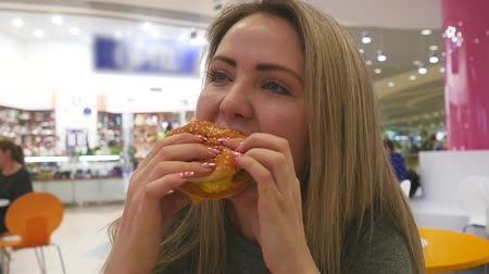 hambúrguer : Portrait of a close-up girl with a hamburger in her hands. Young attractive woman eating a hamburger.