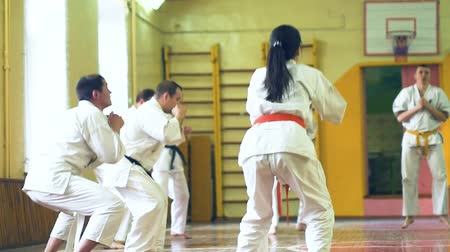 zapasy : Russia, Novosibirsk, August 15, 2018 A group of people practicing karate strokes indoors. Endurance training in karate