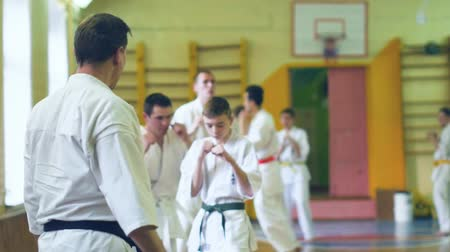 antrenör : Russia, Novosibirsk, August 15, 2018 A group of people practicing karate strokes indoors. Endurance training in karate