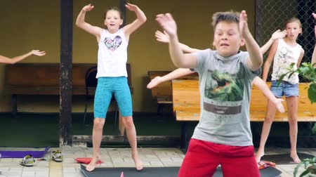 nurture : Russia, Anapa, 2018: Children do morning exercises under the guidance of an outdoor trainer Stock Footage