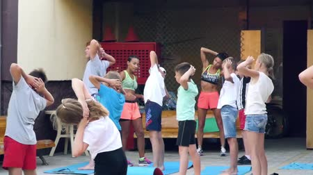 antrenör : Russia, Anapa, 2018: Children do morning exercises under the guidance of an outdoor trainer Stok Video
