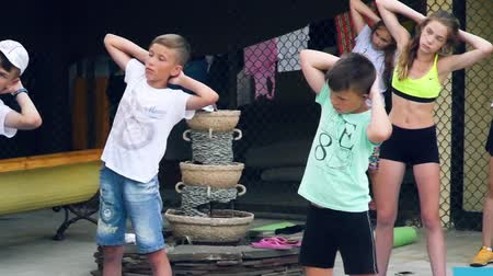 Russia, Anapa, 2018: Children do morning exercises under the guidance of an outdoor trainer Stok Video