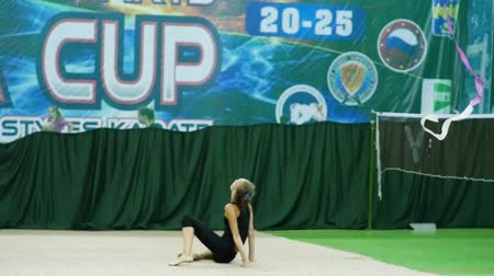 Russia, Anapa, 2018: Cute and flexible little girl performing the gymnastics, does forearm stand split, rolls on the floor and stands up. Contemporary body art, being fit and healthy.