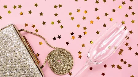 giveaway : Festive evening golden clutch and champagne glass with star sprinkles shining on pink. Holiday and celebration background. Luxury accessories and party concept Stock Footage