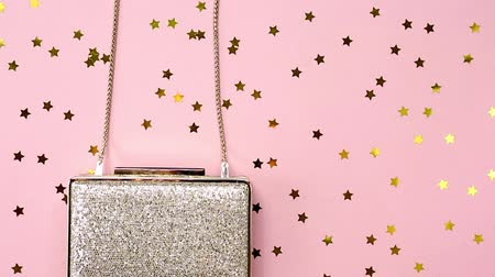 giveaway : Festive evening golden clutch with star sprinkles on pink. Holiday and celebration background. Luxury accessories and party concept