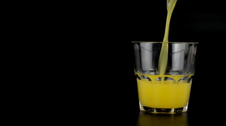 fresh orange drink lemon juice poured into a glass on a black background Stock mozgókép