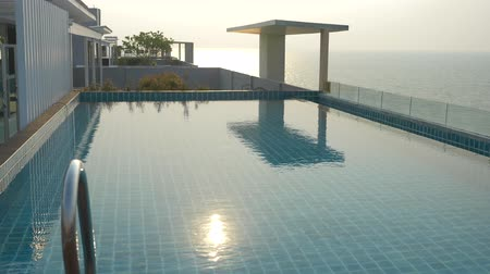 moderní : a luxurious pool on the roof of the house with a sea view. On the Sunset. 4k, slow motion, solar glare on the water. background blur