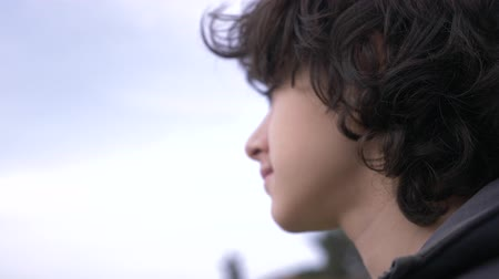 тревожный : Cute teenager with curly hair against the blue sky 4k, slow-motion shooting
