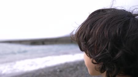 тревожный : A cute teenager with curly hair against the backdrop of the sea. 4k, slow motion