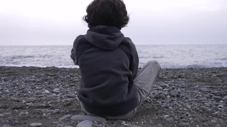 unrequited : A lonely boy sits on the shore and throws stones at sea. 4k, slow motion
