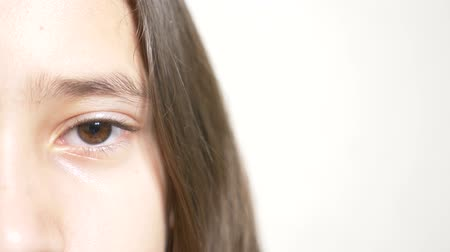 haughty : Young sad girl looks at the camera. 4k. Slow motion, close-up half face, eye close-up. copy space