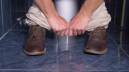 clyster : the feet of a man who sits in the toilet with a pain in his stomach. 4k, close-up, man in trousers and shoes in the toilet Stock Footage