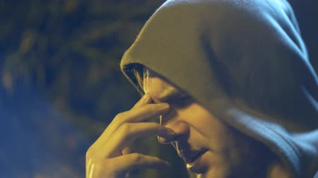 chagrin : Profile of a sad man with a hood. close-up, background blur, bokeh. 4k