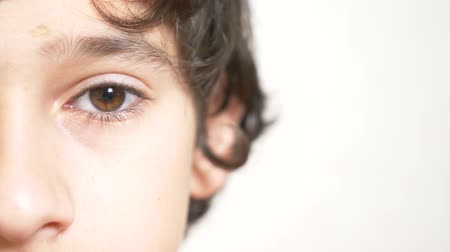 haughty : A young boy looks at the camera . 4k. close-up, half face, copy space. Slow motion