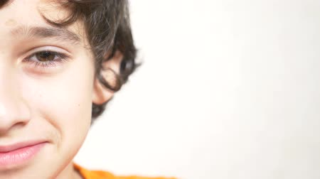 haughty : A young boy looks at the camera and smiling. 4k. close-up, half face, copy space. Slow motion Stock Footage
