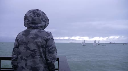 mariner : someone in a hooded jacket is standing on the pier and watching the sailboats sailing to the sea. 4k, slow motion. Stock Footage