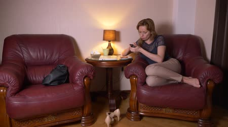 livingroom : woman uses a cellphone at night and eats snacks while sitting in a chair at home. 4k, blur the border of the frame.