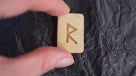 vikings : rune. close-up, hand puts the rune on the surface for divination. 4k, slow-motion Stock Footage