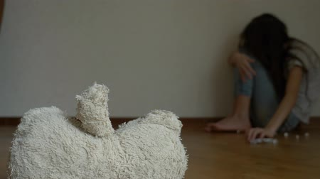 refah : a desperate child in depression sits at the wall of his room, tries to attempt suicide. next to it is an abandoned soft toy. 4k, slow motion.