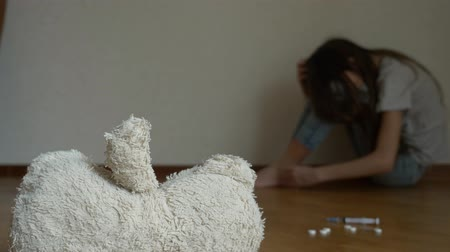 neglected : a desperate child in depression sits at the wall of his room, tries to attempt suicide. next to it is an abandoned soft toy. 4k, slow motion.