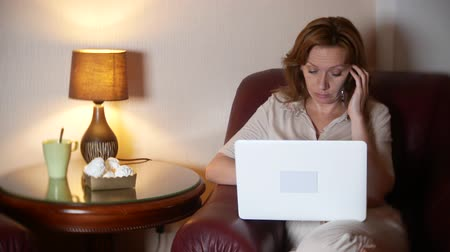 woman working at night on laptop and eating snacks, sitting in armchair at home. 4k, blur the border of the frame.
