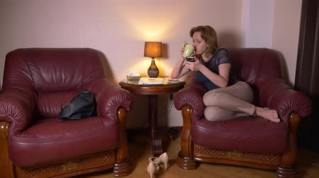woman uses a cellphone at night and eats snacks while sitting in a chair at home. 4k, blur the border of the frame.