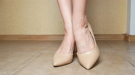 kotník : close-up. female legs in creamy high-heeled shoes. indoors. 4k Dostupné videozáznamy