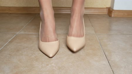 expression of emotions, body language. a woman stomps her foot on the floor, indignation, anticipation. close-up. female legs in creamy high-heeled shoes. indoors. 4k