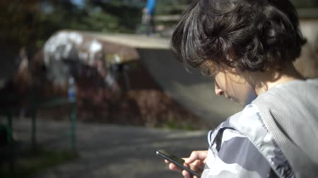 karga : A boy alone using a mobile phone outdoors. while other children have active rest. Smartphone addiction. 4k, slow motion