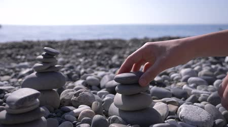 empilhamento : close-up, hand folds a pyramid of stones on the seashore. 4k, slow motion