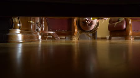 glare : 4k, slow motion, view from under the bed. A woman with a flashlight is looking for something under the bed.