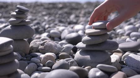 стенд : close-up, hand folds a pyramid of stones on the seashore. 4k, slow motion