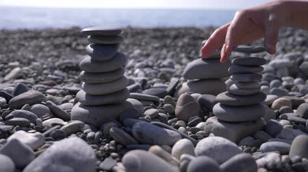стабильность : close-up, hand folds a pyramid of stones on the seashore. 4k, slow motion