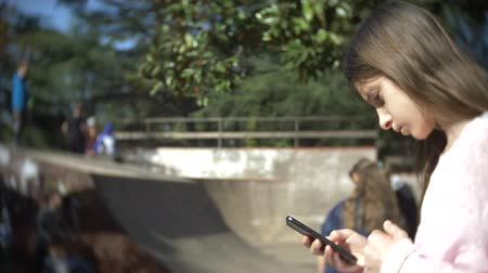 karga : A girl alone using a mobile phone outdoors. while other children have active rest. Smartphone addiction. 4k, slow motion