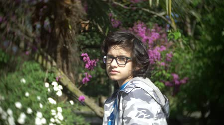 haughty : Portrait of a boy wearing glasses, looking at the camera in a summer park. 4k. slow motion Stock Footage