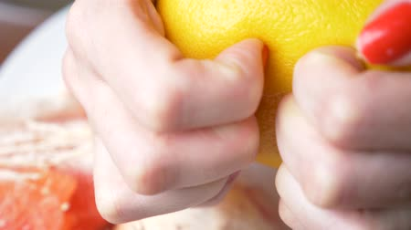 fruitarianism : Female hands cleanse the grapefruit. 4k, close-up, slow-motion