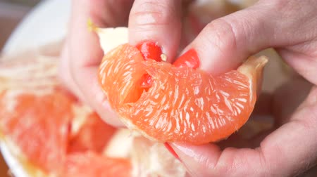 grejpfrut : Female hands cleanse the grapefruit. 4k, close-up, slow-motion