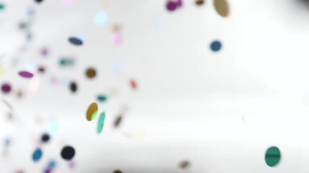 kék háttér : super slow-motion shooting. round multicolored confetti fall and whirl in the air.