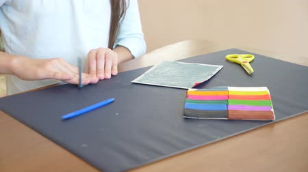 gravura : the girl sitting at the table, draws different figures from color model plasticine. Development of art modeling in children. 4k, close-up, slow-motion